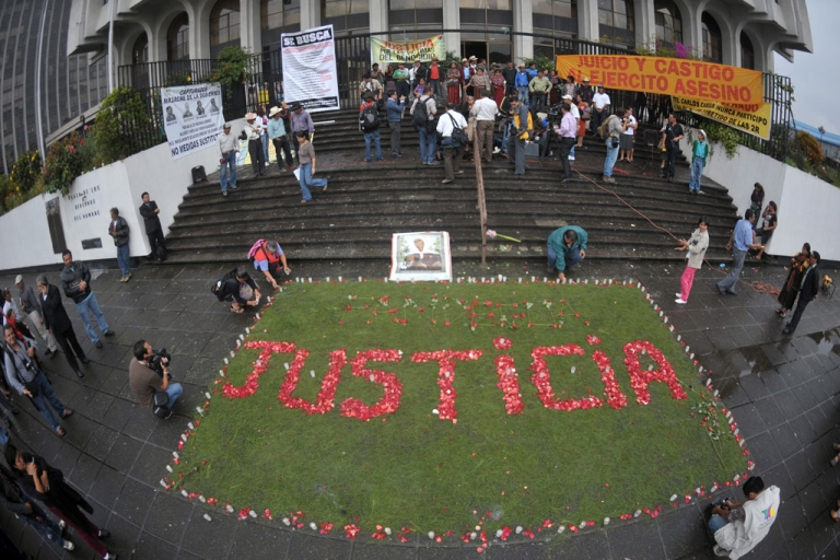 <p>Relatives of the victims of the slaughter of the villa Dos Erres form the word 'Justice' with flowers outside the Supreme Court on Aug. 2, 2011 in Guatemala City before the trial of military men involved.</p>