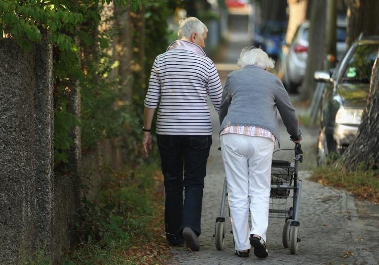 <p>Two elderly women walk along a street in Berlin, Germany, on Sept. 18, 2012.</p>