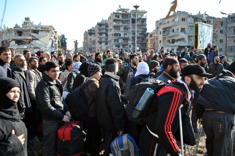 <p>Civilians wait to be evacuated by UN staff, from the besieged Syrian city of Homs, Feb. 9, 2014.</p>