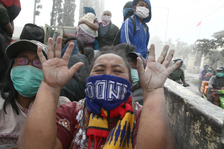 <p>A woman gestures during the evacuation in Malang, East Java province, on Feb. 14, 2014 moment after Mount Kelud eruption.</p>
