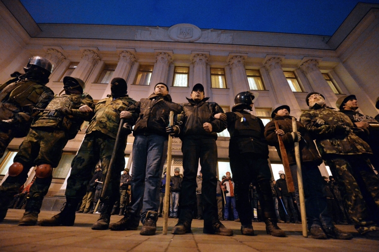 <p>Self-defense activists stand guard in front of parliament during a session on Monday as EU leaders arrived in Kyiv. Ukraine has appealed for urgent international aid, saying it needs $35 billion over the next two years.</p>