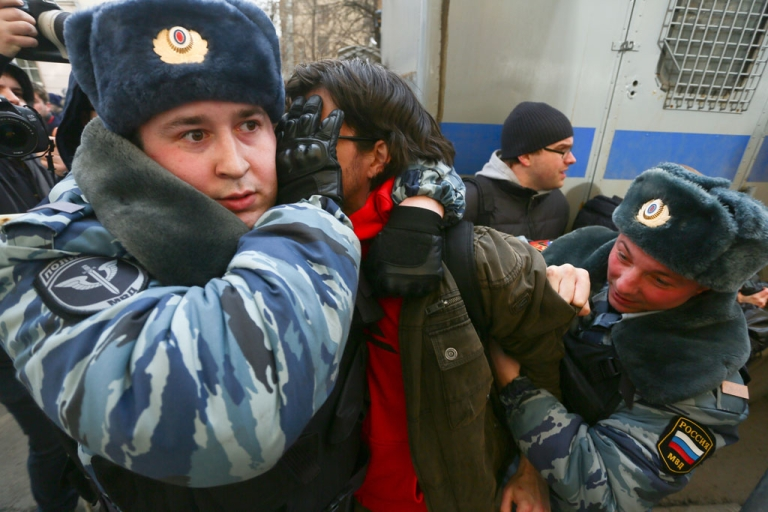 <p>OMON (riot police) officers detain a protester outside a court in Moscow on February 21, 2014. Protesters gathered outside the trial of eight people found guilty of rioting during the Bolotnaya Square demonstrations in 2012.</p>
