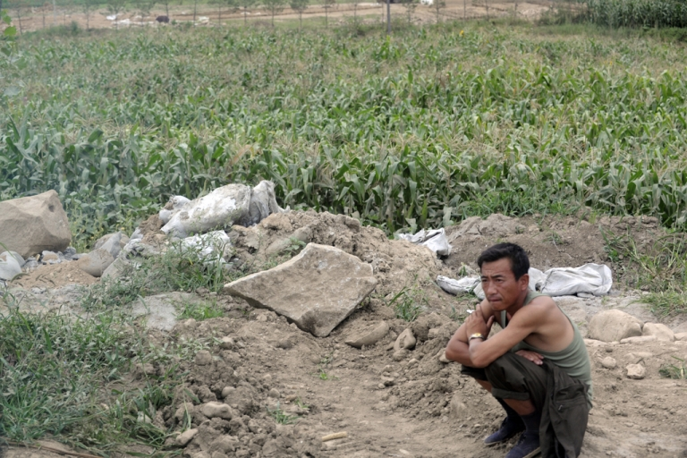 <p>A farmer rests beside his field in the outskirts of Rason city in North Korea on Aug. 29, 2011.</p>