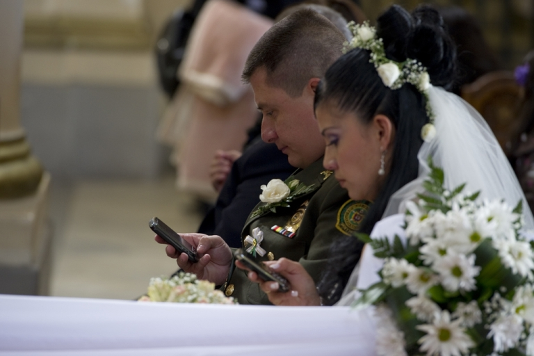 <p>A bride and groom use their mobile phones at the Cathedral of Bogota, Dec. 9, 2011.</p>