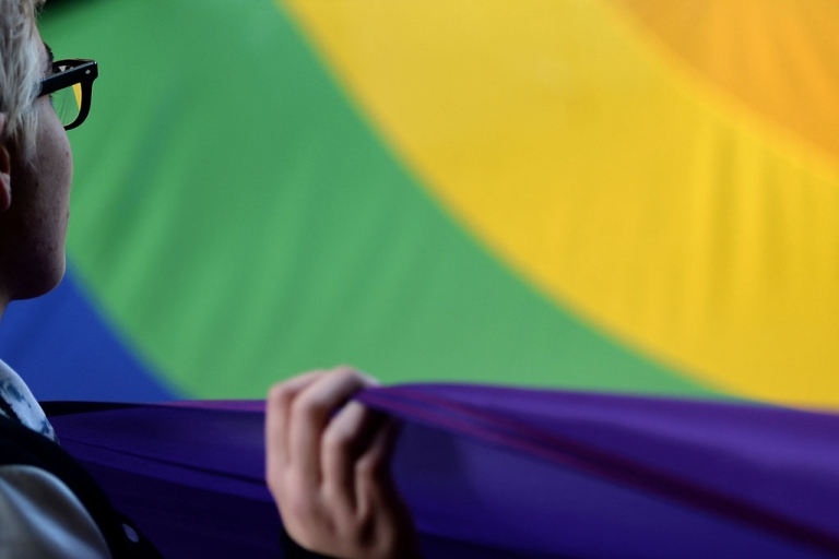 <p>An activist holds up a rainbow flag as people demonstrate outside the Russian embassy in Rome against recent anti-gay legislation ahead of the start of the Winter Olympics in Sochi on February 7, 2014.</p>