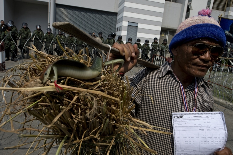<p>A Thai farmer carries bales of rice as he protests against the government's delayed rice subsidy payments. The scandal could bring down the Thai prime minister.</p>