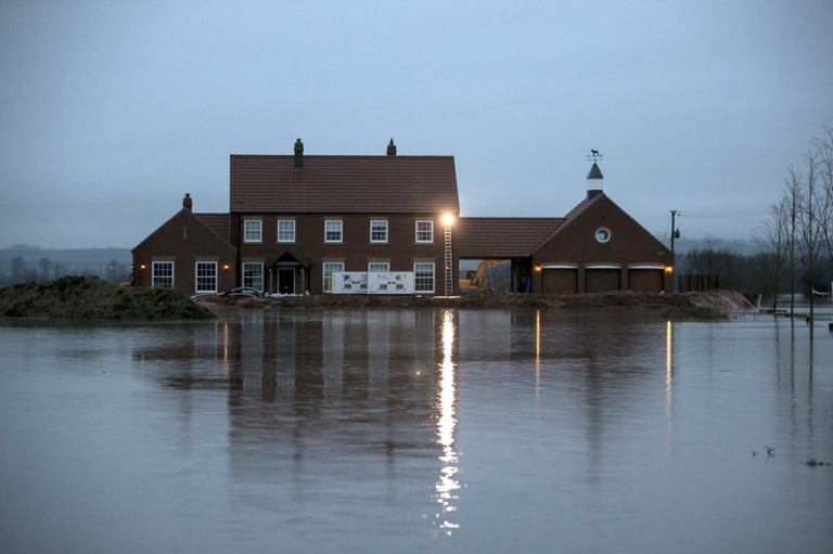 <p>Rising flood waters surround a house in the village of Moorland on the Somerset Levels near Bridgwater, England.</p>