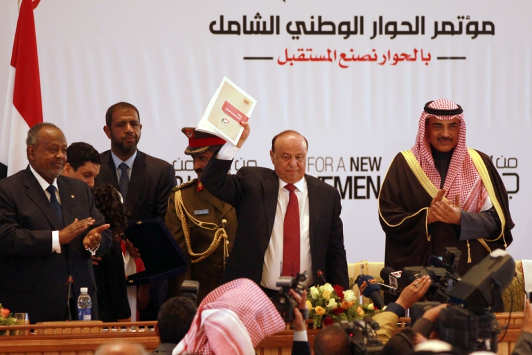 <p>Yemen's President Abd-Rabbu Mansour Hadi (C) shows the book of the national dialogue at the end of a conference aimed at drafting a new constitution and establishing a federal state on Jan. 25, 2014 in Sanaa.</p>