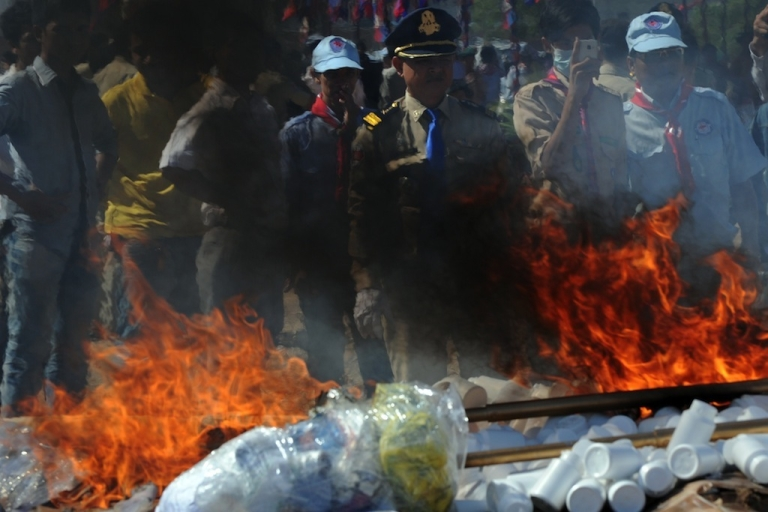 <p>A Cambodian police looks at the flame and smoke from burning drugs during a destruction ceremony in Phnom Penh on August 28, 2012. Cambodian authorities burned more than one ton of drugs.</p>
