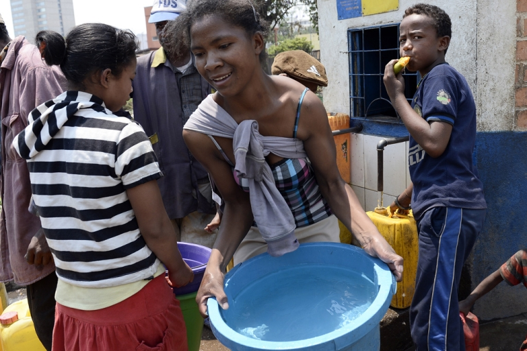 <p>A woman carries water in 'La Reunionkely' area in Antananarivo, Madagascar.</p>