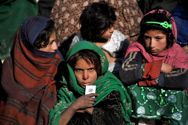 <p>Afghan children wait for relief supplies at a refugee camp on the outskirts of Kabul. Authorities said a girl, possibly as young as eight, tried to carry out a suicide bombing attack on January 5, 2014.</p>