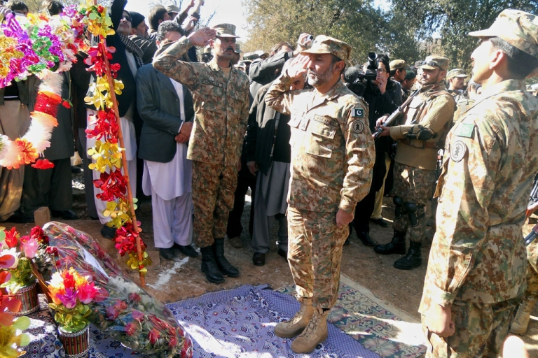 <p>Pakistani army personnel salute after placing flowers at the grave of student Aitzaz Hassan in Hangu, Khyber Pakhtunkhwa, on January 11, 2014. Hassan, 15, sacrificed his life to stop a suicide bomber, saving the lives of hundreds of students, and has been handed the country's highest award for bravery.</p>
