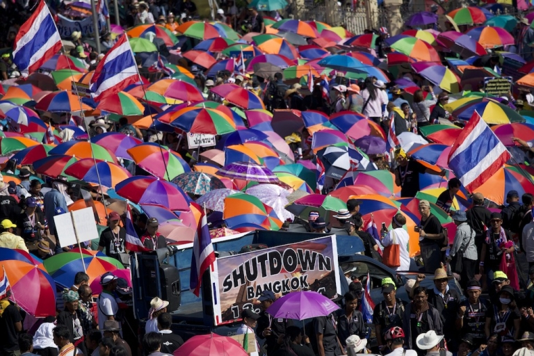 <p>Demonstrators wave flags and hold sun umbrellas on Jan. 13, the first day of the