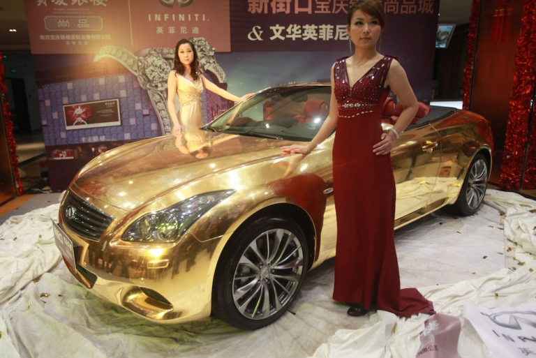 <p>Models pose with a gold-plated Infiniti luxury sports car at a jewellery store in Nanjing. China is predicted to become the world's largest luxury goods market by 2020, but many of the country's wealthy are choosing to emigrate abroad, according to a new study.</p>