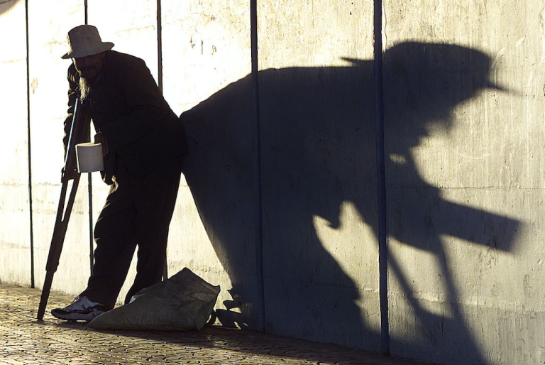 <p>A beggar in Beijing casts a long shadow as he waits for change from inside a Beijing underpass, in 2001. Western journalists often credit the Chinese Communist Party with