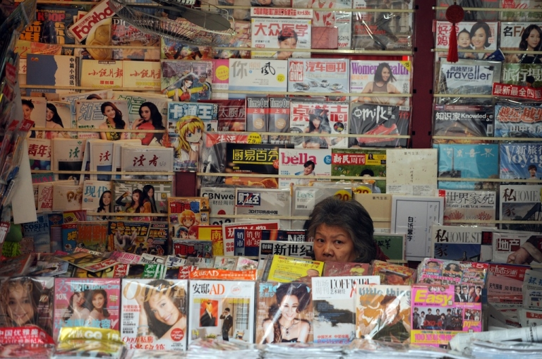 <p>A newspaper vendor looks out from her booth on a street in Shanghai on Jan. 8, 2013.</p>