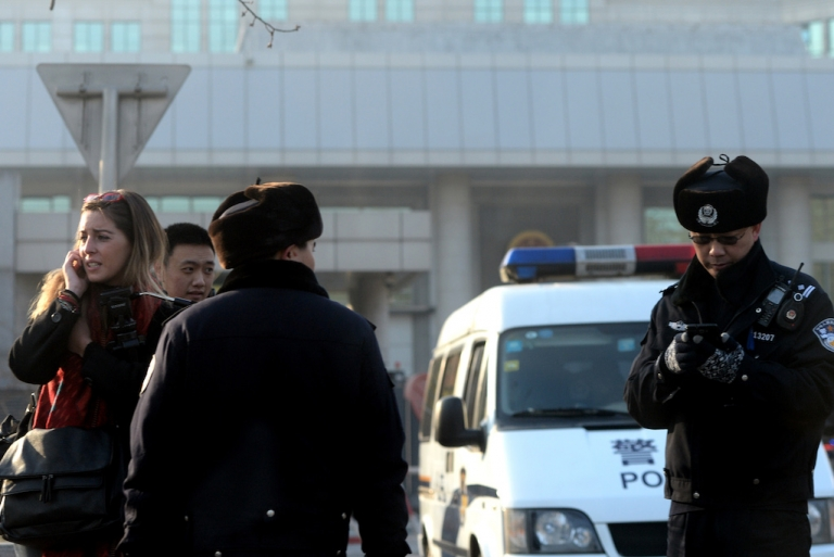 <p>Chinese police stop a foreign journalist outside the trial of Xu Zhiyong on January 22, 2014, under strict security. Xu, one of China's most prominent anti-corruption activists, called for the government to publish the assets of officials. Today, the International Consortium of Investigative Journalists revealed extraordinary overseas wealth of Chinese elites.</p>