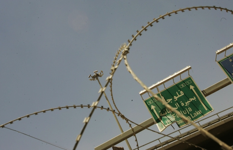<p>Razor wire marks the entrance to Entry Control Point 1, a US Marine guarded entry into the city June 25, 2005 in Fallujah, Iraq.</p>