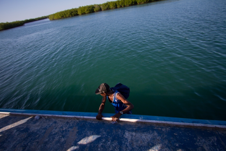 <p>A man walks along the rim of a ferry at the wharf in Anse-a-Galets on Haiti's island of La Gonave.</p>