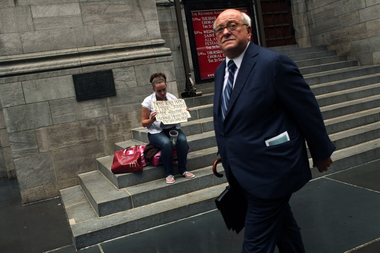 <p>A businessman walks by a homeless woman holding a card requesting money in New York City.</p>