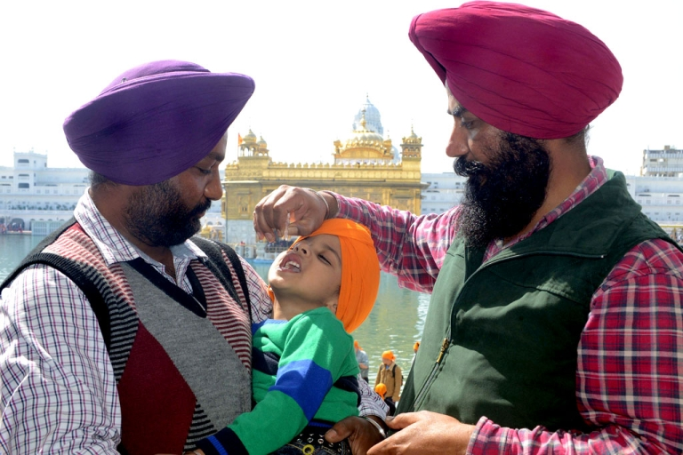 <p>An Indian Sikh boy receives polio vaccination drops from a medical volunteer during an immunisation drive outside the Golden Temple in Amritsar on February 24, 2013.</p>