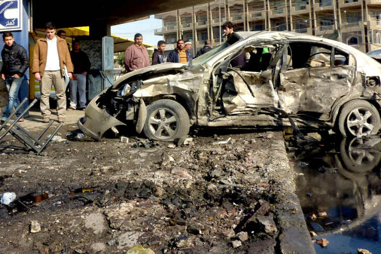 <p>Iraqis gather at the site of a car bomb in central Baghdad, on January 15, 2014. Attacks in Iraq have killed at least 59 people officials said.</p>
