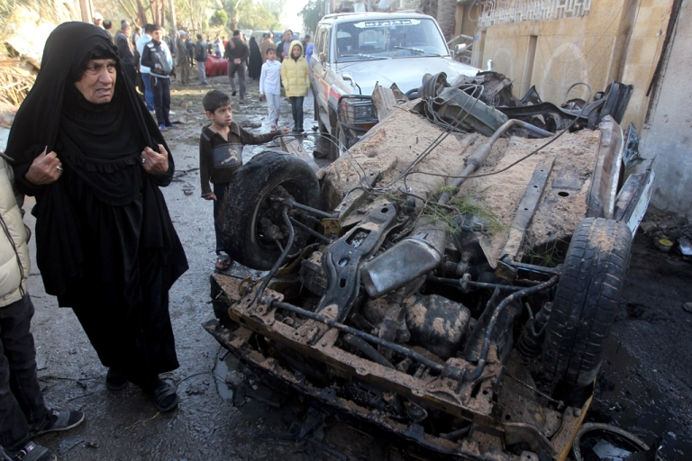 <p>Iraqi civilians gather at the site of the aftermath of a car bomb explosion in the Shuala area of the Iraqi capital Baghdad on January 30, 2014.</p>