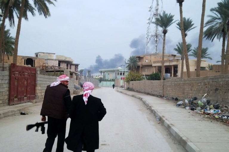 <p>Armed tribesmen stand guard in a street as clashes rage on in the Iraqi city of Ramadi, West of Baghdad, on January 2, 2014. Iraqi special operations forces were fighting in the city of Fallujah, half of which is reportedly under the control of militants linked to Al Qaeda, their commander said.</p>