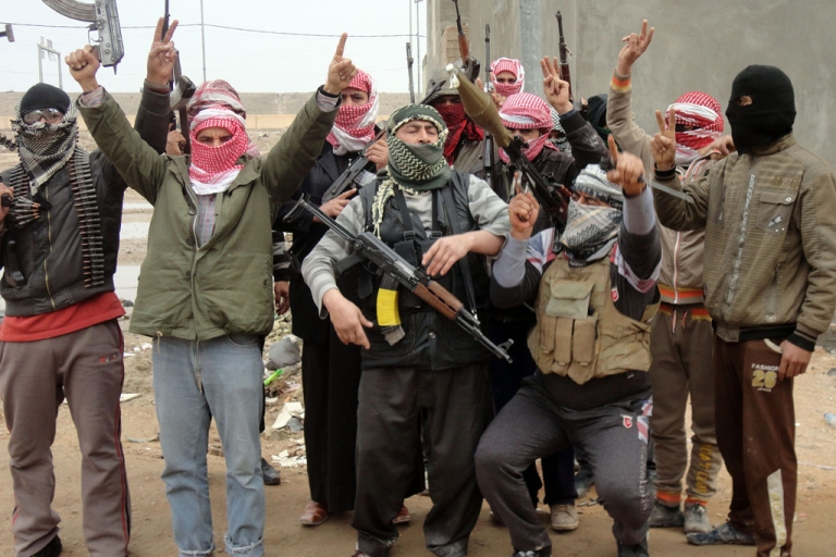 <p>Iraqi men from local tribes brandish their weapons as they pose for a photograph in the city of Fallujah, west of the capital Baghdad, on January 5, 2014.</p>
