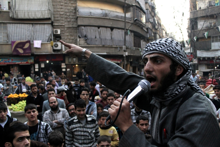 <p>A member of the Islamic State of Iraq and the Levant (ISIL) speaks into a microphone urging people to join their fight against the regime, in the northern Syrian city of Aleppo on November 13, 2013. Syrian troops advanced on the Islamist-held northern village of Tal Hassel, prompting jihadist rebels in nearby Aleppo to call for mass mobilization to counter the offensive. AFP PHOTO/MAHMUD AL-HALABI</p>