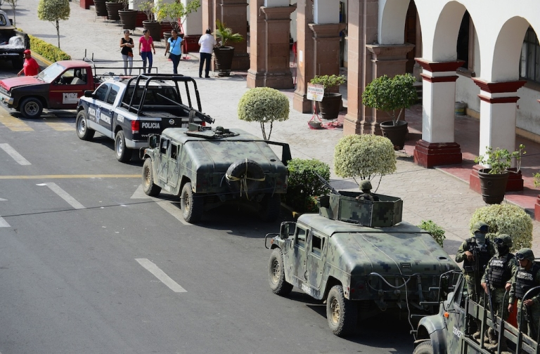 <p>A convoy of army vehicles is parked outside the town hall of Apatzingan, a key stronghold of the Knights Templar cartel, in Michoacan state, Mexico, on Jan. 16, 2014.</p>