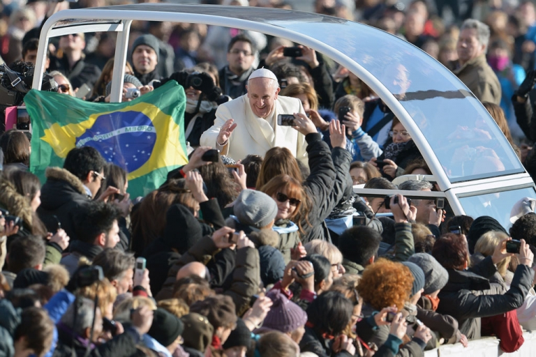 <p>Pope Francis waves to the admirers as he arrives at St. Peter's Square at the Vatican for his weekly general audience on January 8, 2014.</p>