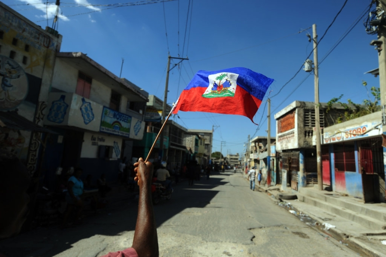 <p>A man holds a Haitian flag as he takes part in a protest demanding that Haitian President Michel Martelly step down in Port-au-Prince on January 13, 2014. The protesters walked from one sector of the center of the capital to the parliament, where Martelly was to deliver a speech on the country's political and economic situation.</p>