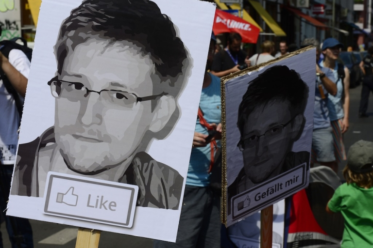 <p>Demonstrators hold placards featuring Edward Snowden as they take part in a protest against the NSA collecting German emails, online chats and phone calls and sharing some of it with the country's intelligence services in Berlin on July 27, 2013.</p>