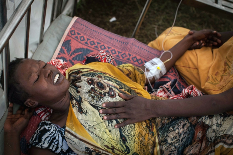 <p>A South Sudanese woman grimaces at a makeshift UN clinic in Juba on January 7, 2014. Thousands of people are fleeing the conflict in South Sudan each day, the United Nations said, as it reported seeing whole villages looted and burned.</p>