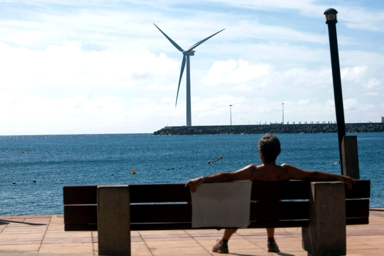 <p>A woman sits on a bench in front of Spain's largest wind turbine, Arinaga. It's located on Gran Canaria in the Spanish archipelago of the Canary Islands.</p>
