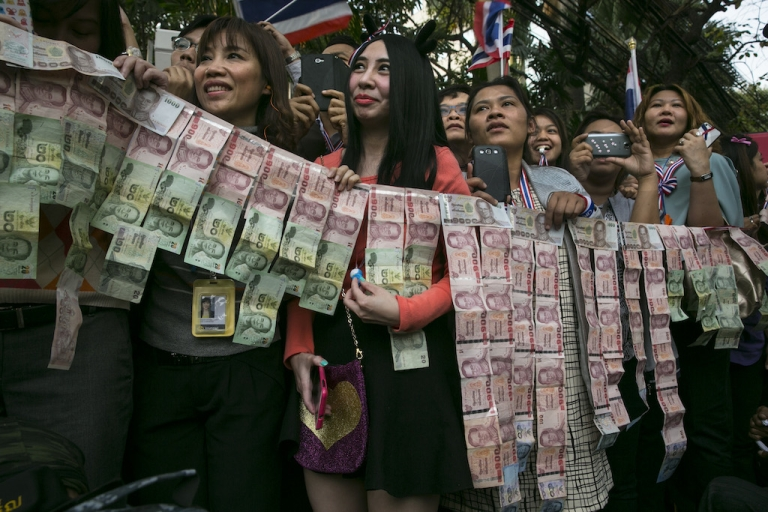 <p>Protesters hold contributions as anti-government leader Suthep Thaugsuban as