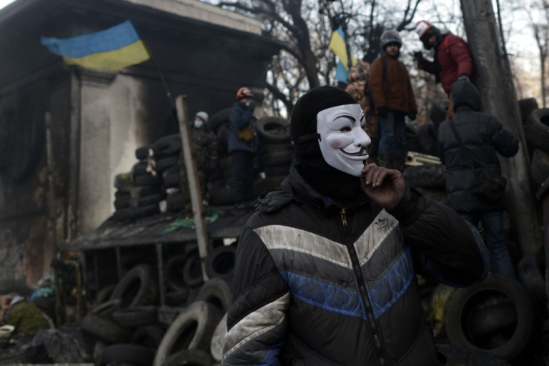 <p>An anti-government protester, wearing a Guy Fawkes mask, rests at a road block in Kyiv on Jan. 26, 2014.</p>