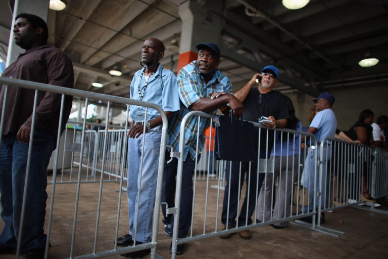 <p>Dale Washington (C) and other people looking for work stand in line to apply for jobs during a job fair in Miami on May 2, 2013.</p>