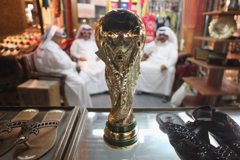 <p>Arab men sit at a shoemaker's stall with a replica of the FIFA World Cup trophy on October 24, 2011 in Doha, Qatar. Qatar will host the 2022 FIFA World Cup.</p>