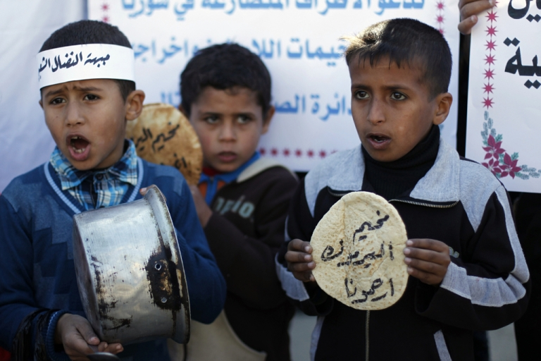 <p>Palestinians children holds bread and pots on January 8, 2014, as they take part in a protest against the poor living conditions at the Yarmuk refugee camp in the Syrian capital Damascus in Gaza Strip.</p>