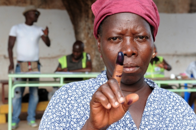 <p>A woman raises her ink-stained finger after voting in the second round of the presidential election on May 18, 2014 in Bissau. Guinea-Bissau voted for a new president on May 18 in a key test for a fragile state plagued by powerful cocaine cartels and upended in a military coup two years ago.</p>