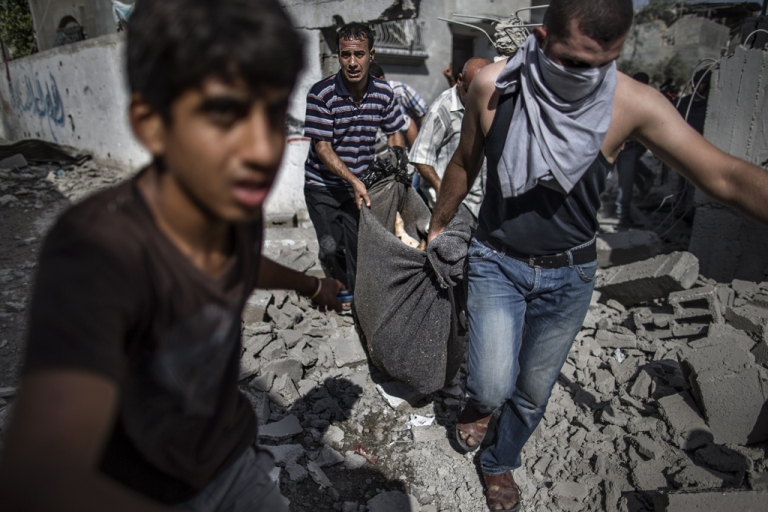 <p>Palestinian recover the body of a man killed when his home was hit the previous night by Israeli fire in the northern district of Beit Hanun in the Gaza Strip during an humanitarian truce, on July 26, 2014.</p>