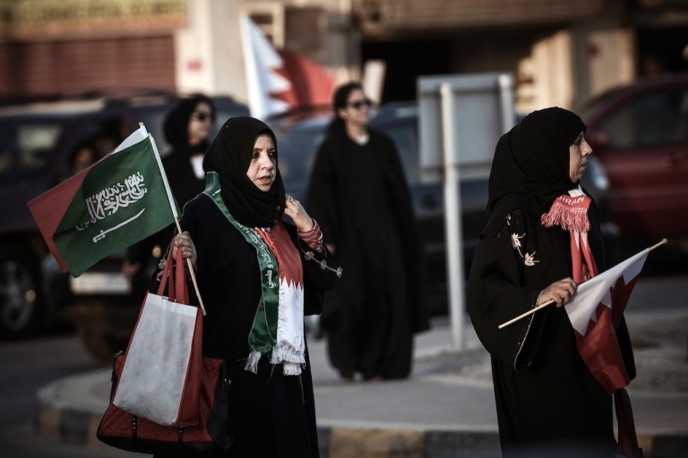 <p>Bahraini women hold Bahrain and Saudi flags during a pro-government rally in the village of Arad on the Bahraini island of Muharraq on February 21, 2013.</p>