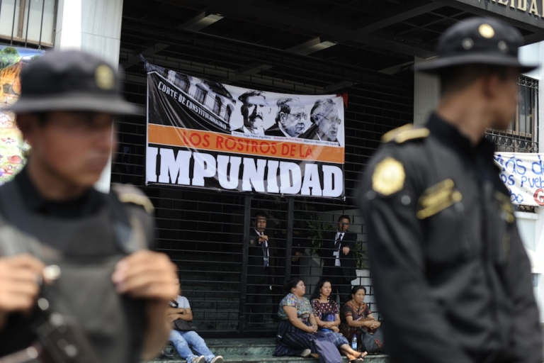 <p>Police officers guard the entrance of the Constitutional Court (CC) of Guatemala, during a protest against the quashing of the 80-year sentence for genocide of former Guatemalan dictator General Efrain Rios Montt on May 24, 2013 in Guatemala city. Rios Montt will go back on trial after the nation's highest court threw out his genocide and war crimes conviction in the latest twist in complex proceedings.</p>