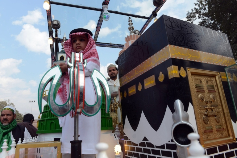 <p>A Pakistani child stands next to a replica of the Kaaba, the Grand Mosque in the holy city of Mecca, during celebrations marking Eid Milad-un-Nabi, the birthday of Prophet Mohammed, in Lahore on January 14, 2014.</p>