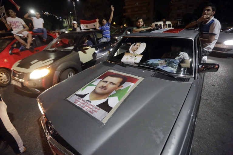<p>Syrians celebrate in a car with a picture of re-elected Syrian President Bashar al-Assad in Damascus.</p>