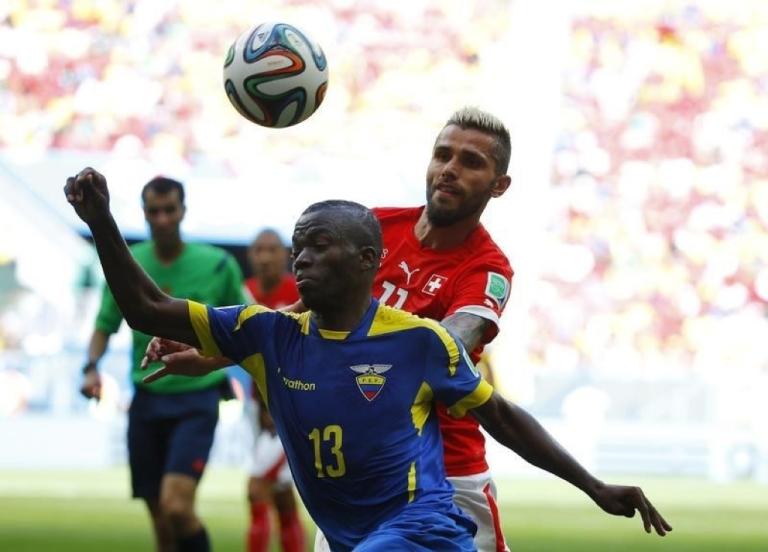 <p>Ecuador's Enner Valencia, front, fights for the ball with Switzerland's Valon Behrami during their 2014 World Cup Group E soccer match at the national stadium in Brasilia, Brazil, June 15.</p>