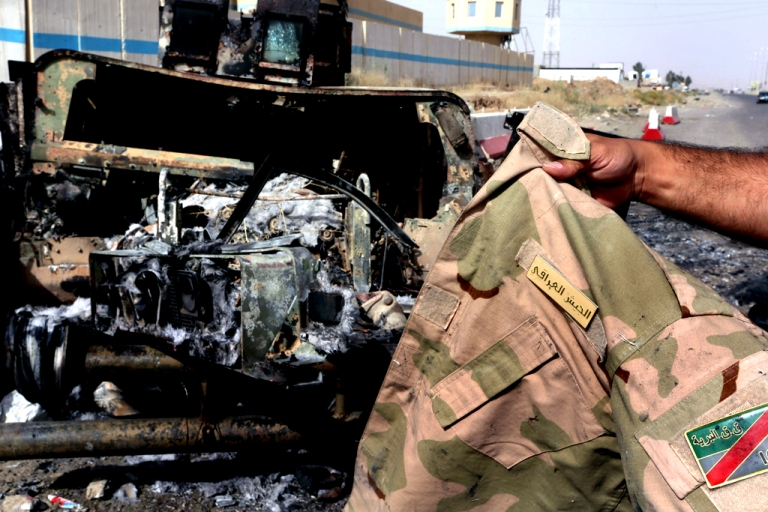 <p>A man displays an Iraqi army jacket in front of a burnt out US-made Iraqi army Humvee vehicle east of the city of Mosul, on June 11, 2014, a day after Sunni militants including fighters from the Islamic State of Iraq and the Levant (ISIL) overran the city.</p>