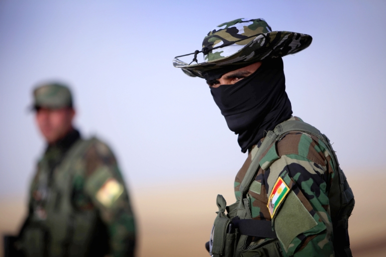 <p>An Iraqi Kurdish soldier stands guard as Iraqi families fleeing violence in the northern Nineveh province gather at a Kurdish checkpoint in Aski Kalak, 25 miles west of Arbil, in the autonomous Kurdistan region, on June 11, 2014.</p>